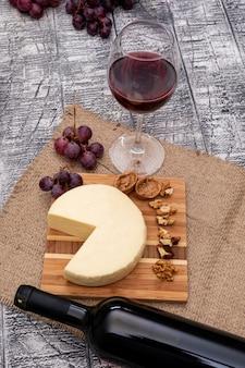 Vista lateral vino con uva y queso a bordo y en vertical de madera blanca