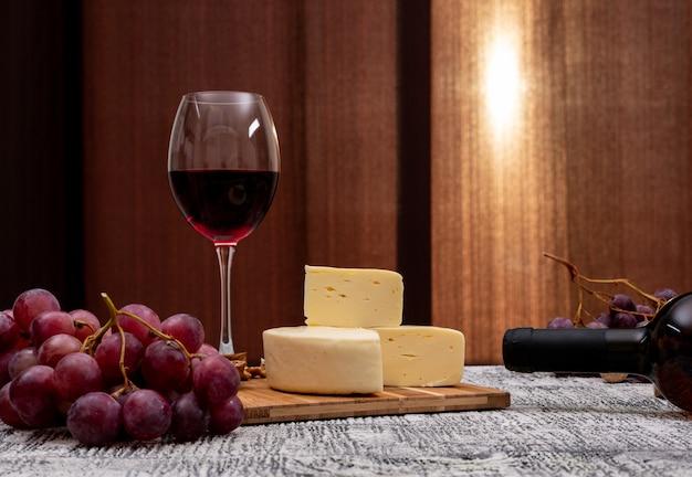 Vista lateral vino con uva y queso en mesa de madera blanca y horizontal