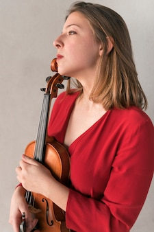 Vista lateral de la violinista femenina posando con violín