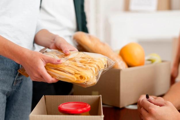 Vista lateral del voluntario preparando caja de donación con comida