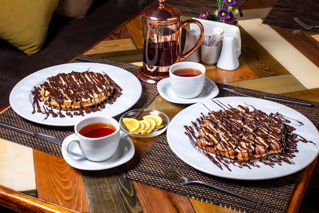 Vista lateral de waffle con plátanos cubiertos de chocolate en un plato blanco servido con té sobre la mesa