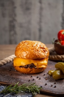 Vista lejana frontal hamburguesa de carne cursi con encurtidos, verduras y tomates en el escritorio de madera