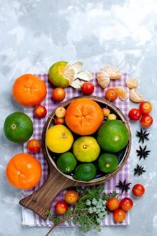 Vista lejana superior agrias mandarinas frescas con limones y ciruelas en el escritorio de color blanco claro cítricos frutas tropicales exóticas vitamina agria