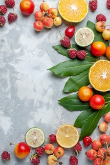 Vista lejana superior limones y cerezas frutas frescas en escritorio blanco claro fruta fresca madura madura