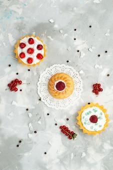 Vista lejana superior little d tortas con crema y diferentes frutas aisladas en la superficie ligera dulce de azúcar
