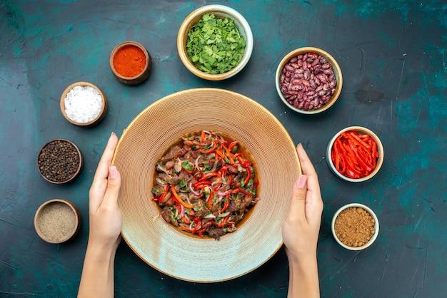 Vista lejana superior de verduras en rodajas con carne haciendo una ensalada con frijoles condimentos verdes en el escritorio azul oscuro, ensalada de carne de comida