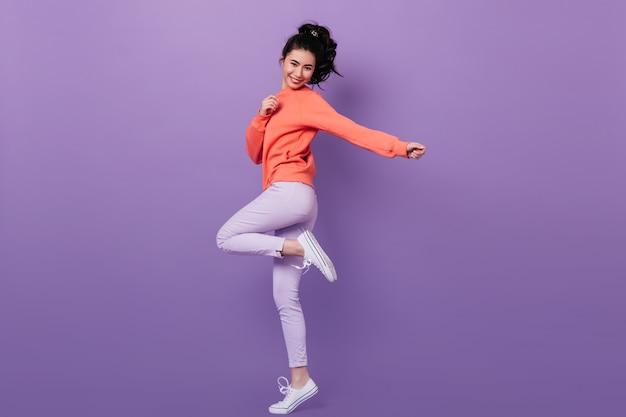 Vista de longitud completa de la alegre niña china de pie sobre una pierna. foto de estudio de modelo de mujer asiática sin preocupaciones bailando sobre fondo púrpura.