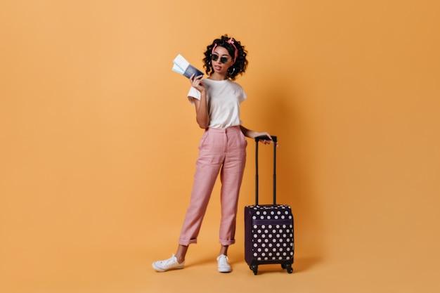 Vista de longitud completa de mujer adorable con maleta y boletos