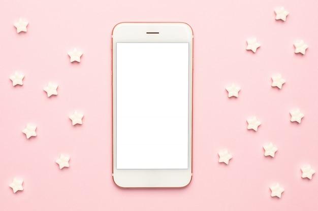 Vista macro de teléfono móvil y piruletas de estrella dulce blanco