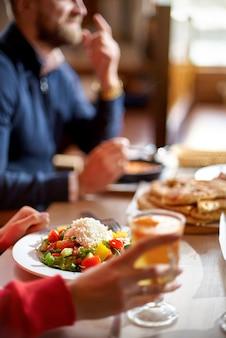 Vista de manos de jóvenes comiendo brunch en un moderno bar restaurante - estilo de vida saludable, concepto de tendencias alimentarias - centrarse en la mano izquierda de la mujer, plato