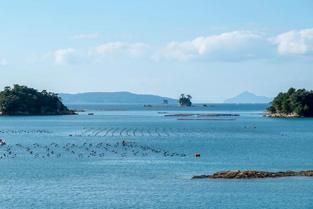 Vista del mar azul y granja de ostras en la isla de kujuku