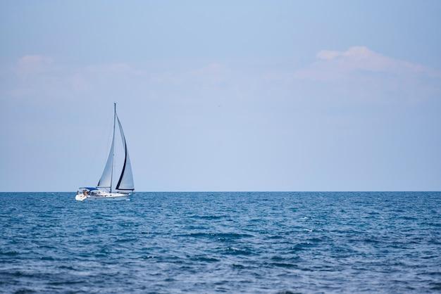 Una vista del mar, un yate blanco con velas y el cielo.