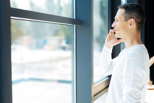 Vista maravillosa. encantado de buen hombre guapo mirando por la ventana y admirando la vista mientras tiene una conversación telefónica