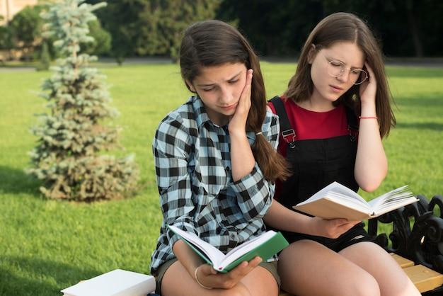Vista media de tiro lateral de chicas de secundaria leyendo en el banco