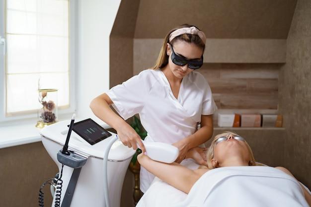 Vista del médico cosmetólogo haciendo un procedimiento anti-envejecimiento en la oficina de cosmetología. mujer satisfecha con sombrero desechable acostado en el sofá y relajante. trabajando con aparato.