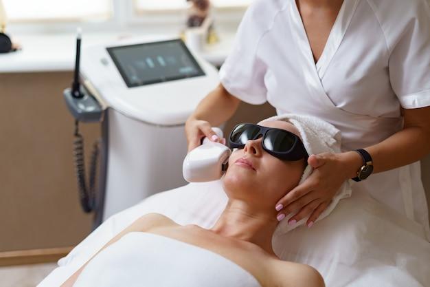 Vista del médico cosmetólogo haciendo un procedimiento anti-envejecimiento en la oficina de cosmetología. mujer satisfecha con sombrero desechable acostado en el sofá y relajante.
