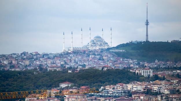 Vista de la mezquita de camlica ubicada en una colina con edificios residenciales en la ladera, torre en la cima de la colina, tiempo nublado, estambul, turquía