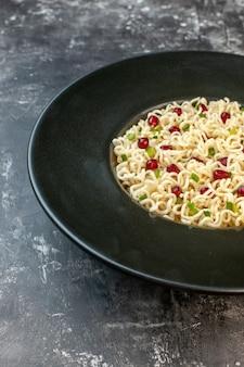 Vista de la mitad inferior de fideos ramen asiáticos en plato redondo negro sobre mesa oscura