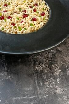 Vista de la mitad inferior de fideos ramen asiáticos en un plato redondo sobre una mesa oscura