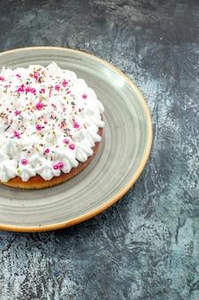 Vista de la mitad inferior de la torta con crema pastelera en un plato redondo gris sobre una mesa gris