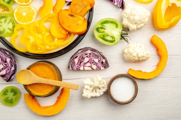 Vista de la mitad superior cortar verduras y frutas calabaza caqui repollo morado limón tomates verdes coliflor pimientos amarillos en un plato negro especias en tazones pequeños sobre la mesa