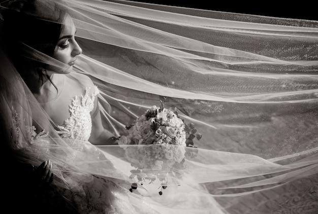 Vista monocroma de una bella novia tierna con ramo de novia y velo largo con los ojos cerrados