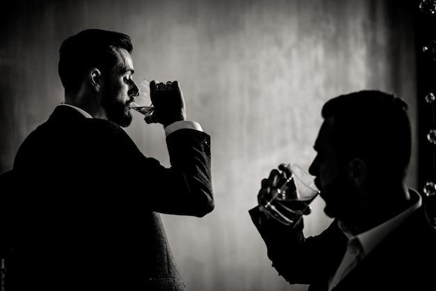 Vista monocroma de dos hombres que toman bebidas alcohólicas en el interior