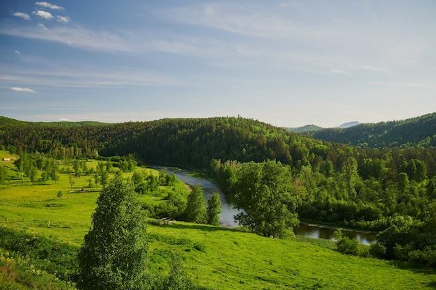 Vista natural de campos verdes en primer plano y montañas de acantilados y colinas.