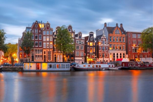 Vista nocturna de la ciudad del canal de amsterdam con casas holandesas