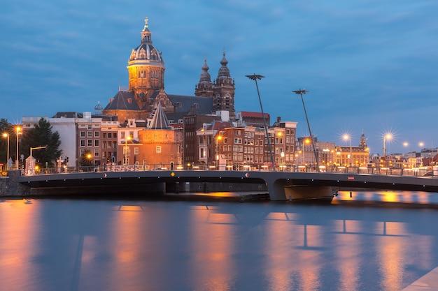 Vista nocturna de la ciudad del canal de amsterdam, el puente y la basílica de san nicolás, holanda, países bajos. exposición prolongada