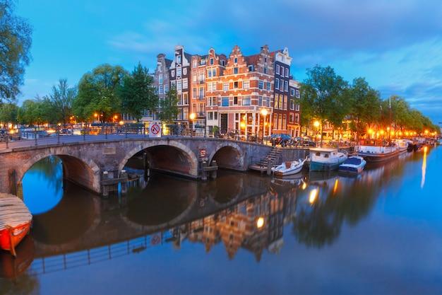 Vista nocturna de la ciudad del canal de amsterdam y el puente