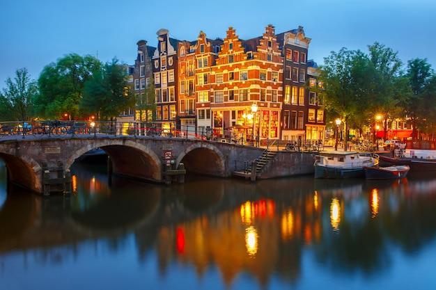 Vista nocturna de la ciudad del canal de amsterdam, puentes y casas típicas, barcos y bicicletas, holanda, países bajos.