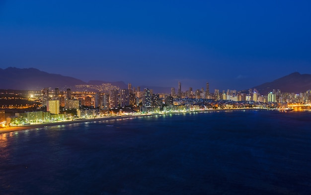 Vista nocturna de la costa en benidorm con luces de la ciudad.