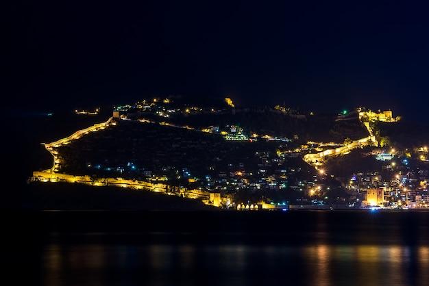 Vista nocturna del puerto y la fortaleza en alanya, turquía