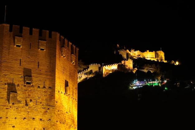 Vista nocturna de la torre roja (kizil kule) y el antiguo muro de piedra del castillo de alanya, turquía