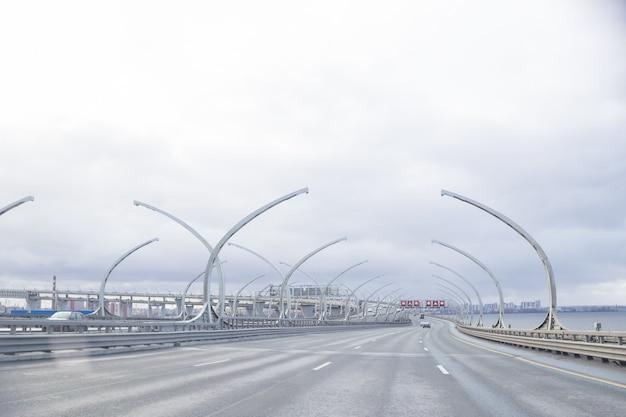Vista del nuevo camino. diámetro occidental de alta velocidad en san petersburgo. cruce de transporte de la ciudad rotonda puesta de sol. línea de carretera. autopista de transporte moderna