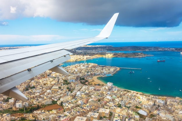 Vista desde el ojo de buey de un avión de pasajeros en la costa de malta con casas típicas.