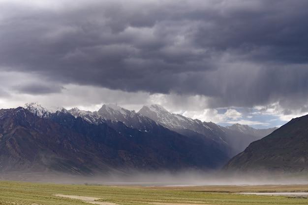 Vista del paisaje del valle de zanskar-padum con las montañas del himalaya cubiertas de nieve y lluvia nublada en jammu y cachemira, india