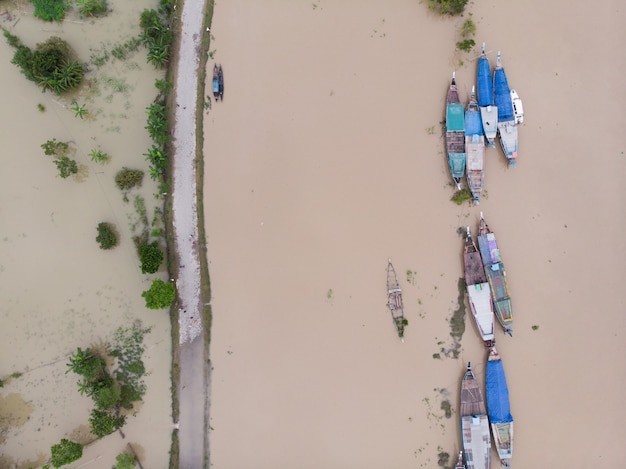 Vista de pájaro de estrechos barcos de madera en un río sucio