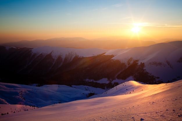 Vista panorámica del atardecer de invierno montañas cubiertas de nieve
