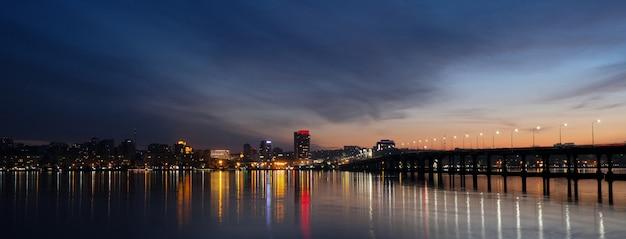 Vista panorámica de la ciudad en la noche cerca del río con reflejo en el agua.