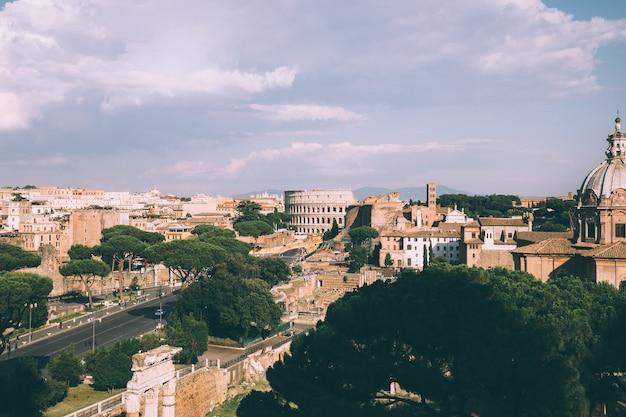 Vista panorámica de la ciudad de roma con el foro romano y el coliseo del monumento a vittorio emanuele ii, también conocido como el vittoriano. día soleado de verano y espectacular cielo azul