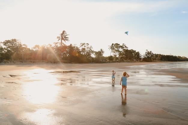Vista panorámica de dos niños caucásicos blancos con cabello rubio jugando con una cometa
