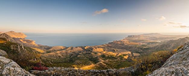 Vista panorámica escénica desde la cima de las montañas hasta la costa del mar, otoño, puesta de sol