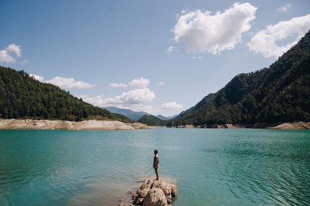 Vista panorámica de un hombre parado sobre una roca en un tranquilo lago de agua azul rodeado de montañas en un día soleado en verano