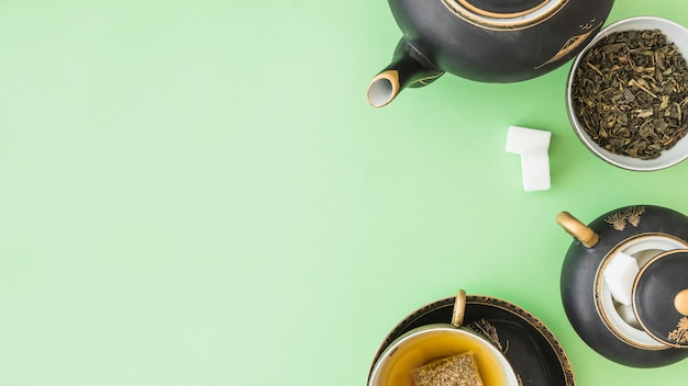 Vista panorámica del juego de té de hierbas con dos terrones de azúcar sobre fondo pastel