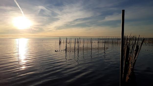 Vista panorámica del lago albufera en valencia, al atardecer, con aguas tranquilas, cerca de las redes de pesca.