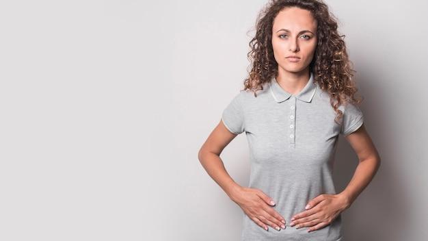 Vista panorámica de la mujer joven que tiene dolor de estómago contra el fondo gris