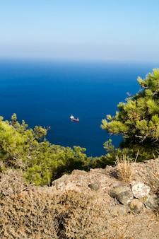 Vista panorámica del océano azul y velero desde el acantilado