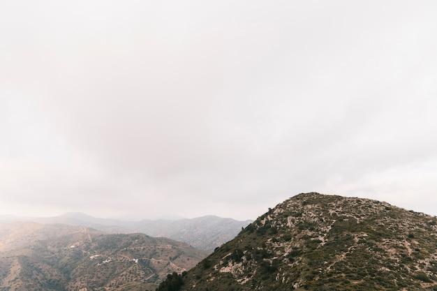 Vista panorámica del paisaje de montañas rocosas con cielo nublado blanco